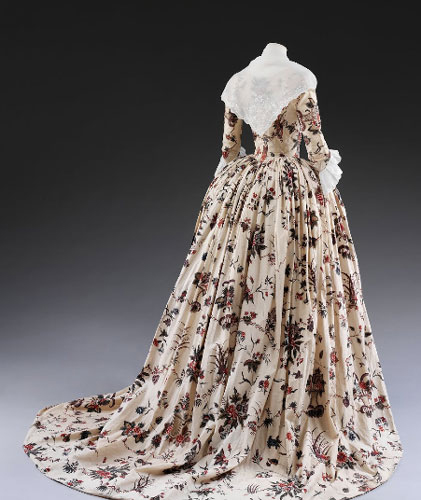 A photo shows the back view of an English-style cotton dress with an intricate floral design displayed on a headless mannequin. Lace frills on the sleeves and neck of the dress are visible.